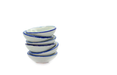 precarious: Stack of small bowls on white background Stock Photo