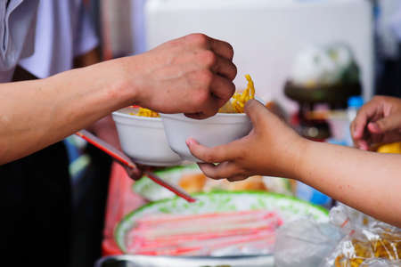 Helping the poor in society by donating food : The concept of hunger Stock Photo