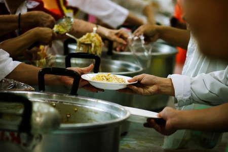 Los voluntarios comparten alimentos con los pobres para aliviar el hambre: concepto de caridad Foto de archivo