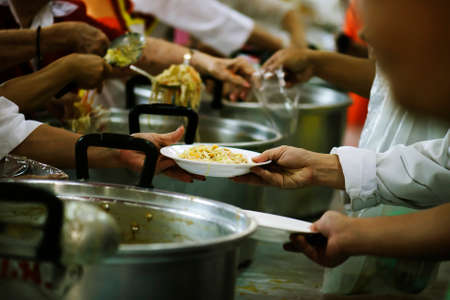 Volunteers Share Food to the Poor to Relieve Hunger: Charity concept Imagens - 110778024