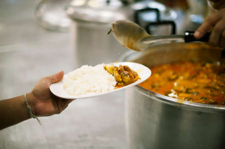 The poor people bring a container to scoop food to eat and relieve hunger and bring home.