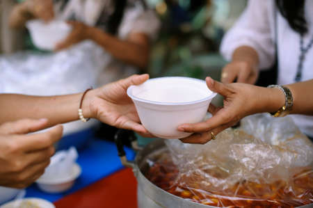 hands of the poor receive food from the donors share. poverty concept