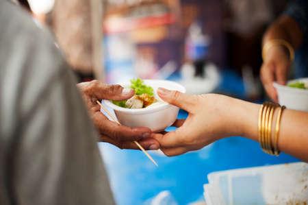 De donatie is een hoop voor hongerige mensen om te vechten: Vrijwilligers delen voedsel aan de armen om honger te verlichten: het concept van delen