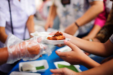 Vrijwilligers zorgen voor voedsel voor bedelaars: concepten Voeden en helpen: concept van het delen van voedsel voor de armen om de honger te stillen: vrijwilligers delen voedsel aan de armen