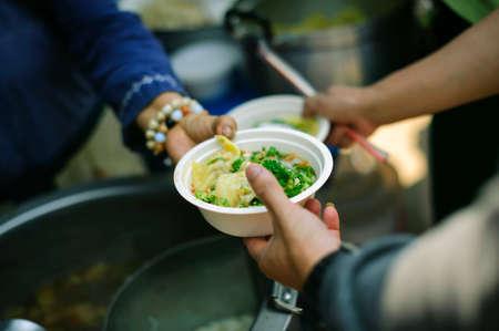 Concept d'alimentation : Les bénévoles donnent de la nourriture aux pauvres : donner de la nourriture, c'est aider les amis humains dans la société : Aider les personnes souffrant de la faim avec gentillesse : le concept des problèmes de la vie, la faim dans la société