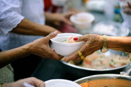 Donate Food with Love and Hope to the Poor: The concept of food is essential to life: the concept of hope: Hand-feeding to the needy in society : Concept of Feeding : Volunteers give food to the poor