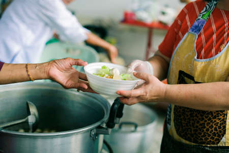 The concept of humanitarianism : The hands of refugees have been aided by charity food to alleviate hunger : Feeding Concepts : Hand offered to donate food from a rich man Share Stock Photo