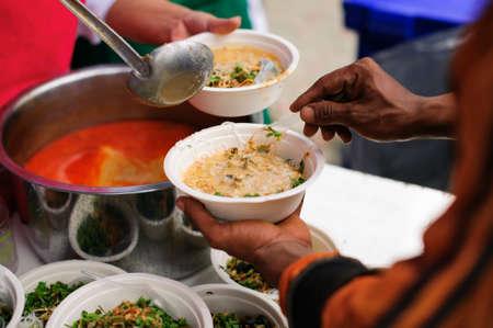 Des mains de bénévoles servent de la nourriture gratuite aux pauvres et aux nécessiteux de la ville : Les pauvres apportent un récipient pour ramasser de la nourriture à manger et soulager la faim et ramener à la maison
