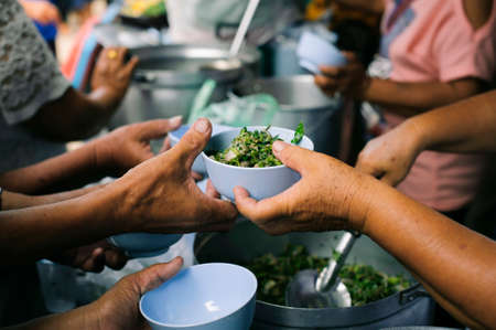 Charity food is free for people in slums : Hands of volunteers serves free food to the poor and needy in the city Stock Photo - 126875936