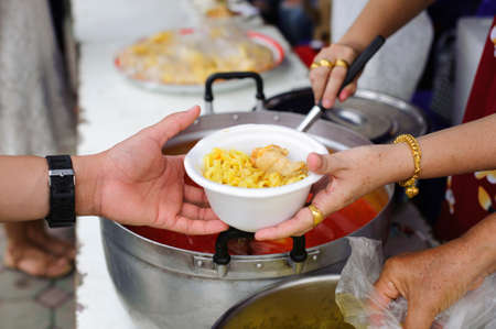 Charity food is free for people in slums : Hands of volunteers serves free food to the poor and needy in the city Stock Photo - 126876338