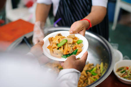 Charity food is free for people in slums : Hands of volunteers serves free food to the poor and needy in the city