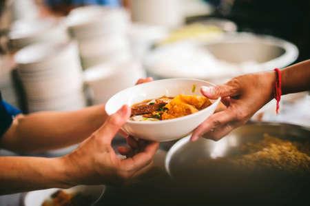 아시아의 가난한 사람들에게 필요한 음식: 거지들이 자선 식품 서비스 제공자에게 음식을 요구하고 있습니다.