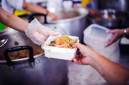 Social hunger: Volunteers provide food assistance to poor people who need food. Stock Photo