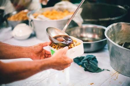 The concept of giving: Homeless people reach out to free volunteer meals from volunteers: help feed the hungry in society.