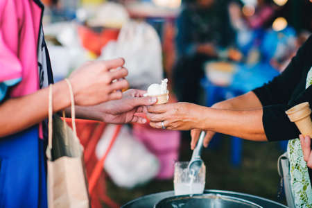 The hands of the poor are waiting to receive food from the rich, compassionate, free food donations to the homeless Stock Photo