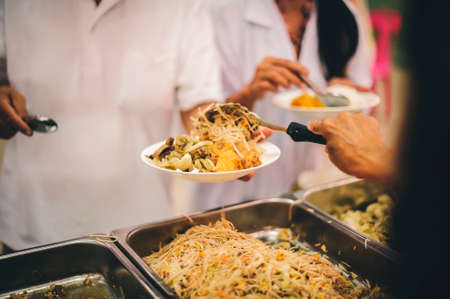 The hands of the poor apply for food from rich people who donate food.