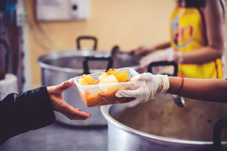 The hand of the wanderer extends to receive food from donations. With volunteers scooping food: the idea of helping with hunger