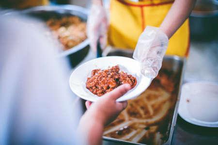 Hands of volunteers serves free food to the poor