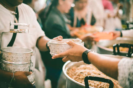 Poor people carrying plates receive food donations from volunteers : The concept of helping