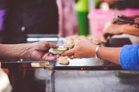 The hands of the poor get free food from the volunteers : the concept of sharing food