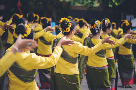 The lady dancing in traditional yellow clothes