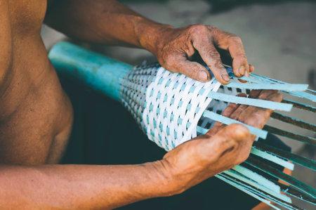 Old senior man hand working crafts basket product