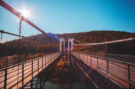 Suspension bridge across the river connects mountains