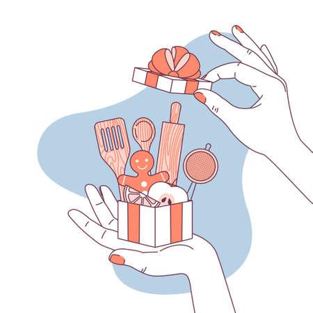 Main de femme tenant un cadeau pour amateur de cuisine. Ustensiles de cuisine.