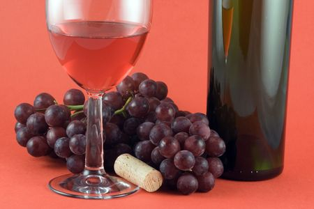 Glass of red wine, grapes and bottle