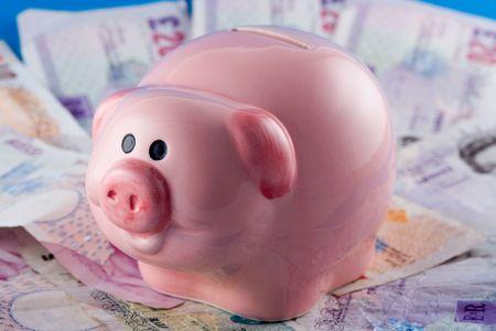 dosh: Piggy bank on a pile of cash