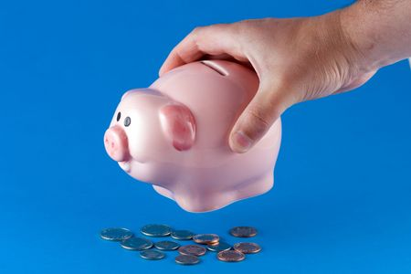 dosh: Shaking a piggy bank to get the coins out Stock Photo