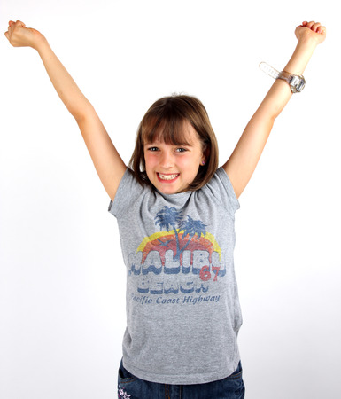 Young girl holding her arms up in celebration Stock Photo