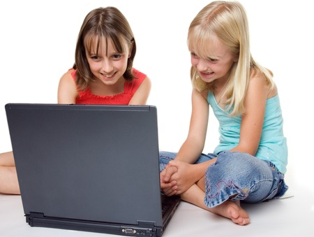 Two yound girls looking ata laptop screen