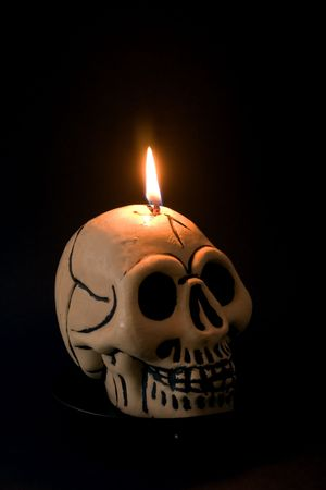 ghoulish: A skull candle against a black background