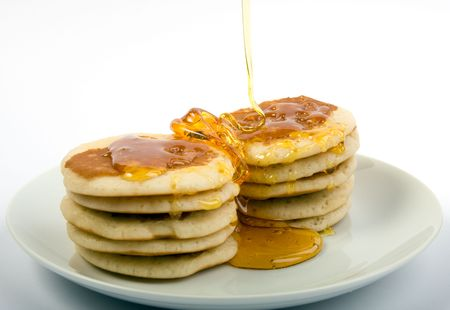 Two stacks of pancakes being drizzled with syrup