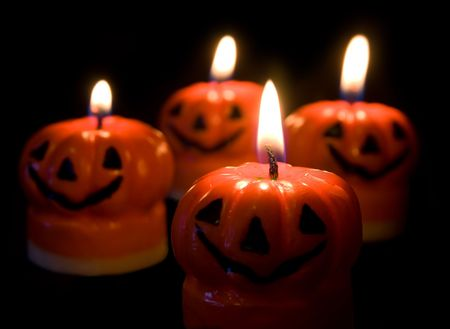 ghoulish: Four lit Halloween pumpkin candles