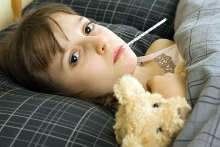 A young girl lying in bed with an illness Stock Photo