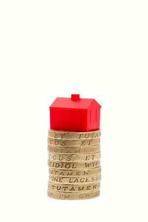 Stack of pound coins with a red plastic house balanced on top Stock Photo