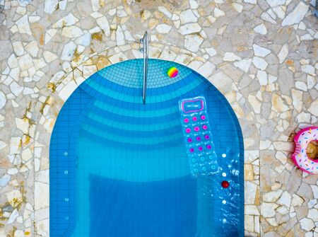 Pool in summer with blue water from above floating inflatables - summer vacation image.?