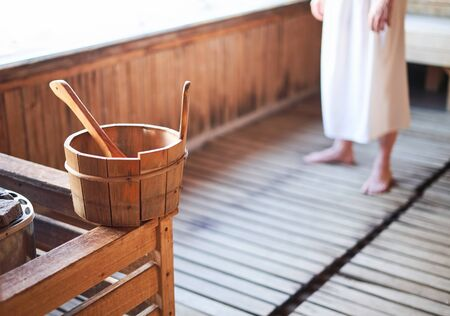 Finnish sauna interior with water bucket. Spa and wellness concept. Copy space for text.