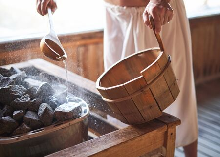 Man pouring water into hot stone in sauna room. Steam on the stones, spa and wellness concept, relax in hot finnish sauna.