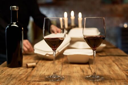 Focus on two glasses of wine. Man preparing for romantic dinner at home. Takeaway delivery food in the background. Ordered food delivery and eating concept.