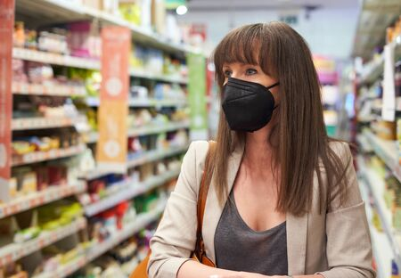 Woman buying groceries in supermarket, wearing black medical face mask while shopping in grocery store. Covid-19 virus prevention. Foto de archivo