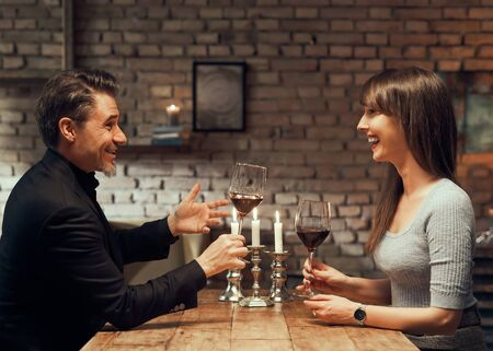 Cheerful couple drinking wine and having romantic dinner at home. Home date night, clinking wine glasses. 免版税图像