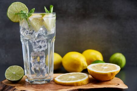 Cold refreshing limonade, mojito or gin tonic in glass, with fresh mint and ice cubes, lime and lemon on wooden board and black background. Summer cocktails and drinks concepts. Copy space for text.
