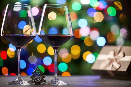 Glasses of red wine, gift box on table, blurred christmas lights in the background.