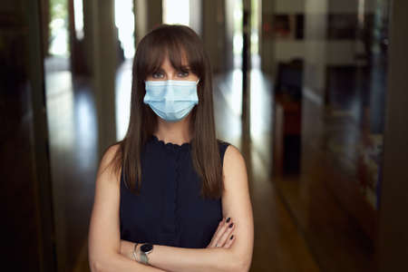 Portrait of happy young female office worker in office building hallway, wearing face mask.