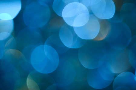 Bokeh photo. Holiday background. Christmas lights. background. Defocused sparkles. New Year backdrop. Festive wallpaper. Blinks. Carnival. Retro style photo. Blue.