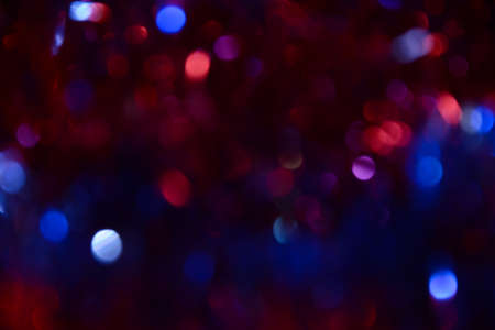 Bokeh. Holiday background. Christmas lights. Glitter. Defocused sparkles. New Year backdrop. Festive wallpaper. Blinks. Carnival. Bokeh retro style photo. Violet. Red. Blue.