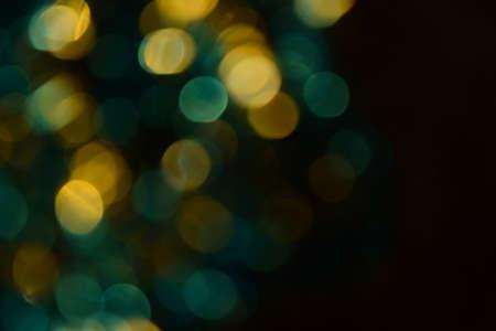 Bokeh. Holiday background. Christmas lights. Glitter. Defocused sparkles. New Year backdrop. Festive wallpaper. Blinks. Carnival. Tinsel. Bokeh retro style photo. Golden. Gold.
